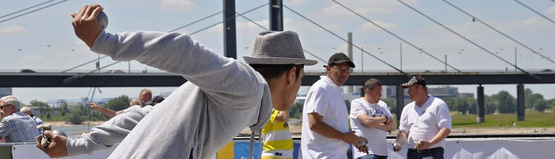 Boulespieler mit gestrecktem Arm vor dem Wurf